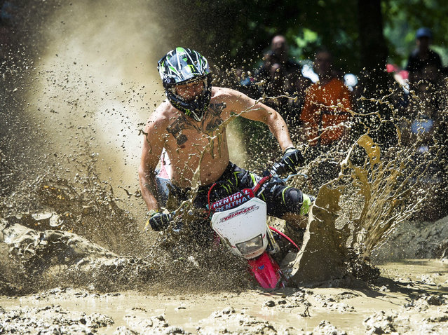 A biker competes in the speeding-in-mud race of the 19th Sirok Bike Week in Sirok, 118 kms northeast of Budapest, Hungary, Saturday, July 28, 2018. (Photo by Peter Komka/MTI via AP Photo)