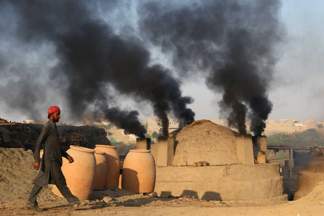 A man stands near smoke billowing from a brick kiln in Karachi, Pakistan, 14 December 2018. According to the UN report, carbon dioxide (CO2) emissions have increased for the first time in four years. The United Nations Conference COP24, held in Katowice, Poland, until 14 December 2018, searches for a common position in the fight against climate change. (Photo by Shahzaib Akber/EPA/EFE)