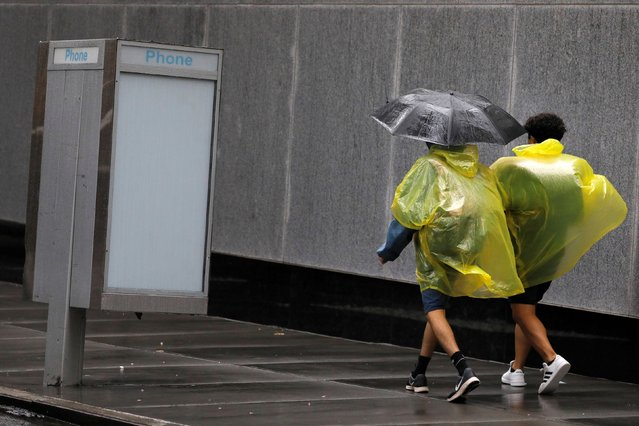 People in plastic rain ponchos walk through the Financial District as Tropical Storm Henri affected the area in Manhattan, New York City, U.S., August 23, 2021. (Photo by Andrew Kelly/Reuters)