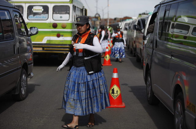 In this December 3, 2013 photo, an Aymara woman cops directs traffic on the streets of El Alto, Bolivia. The women wear the bright petticoats and shawls of indigenous women in the Andes, called cholitas in Bolivian slang, the main difference being that instead of bowler hats they wear khaki green police-style caps. Some don fluorescent traffic vests. (Photo by Juan Karita/AP Photo)