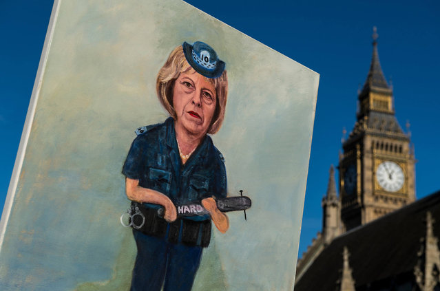 """Artist Kaya Mar holds his latest painting of Theresa May dressed as a police officer holding a truncheon with """"Hard Brexit"""" written on it in front of the Houses of Parliament on January 17, 2017 in London, England. Today in a long awaited speech, British Prime Minister Theresa May outlined the prioirites for the United Kingdom in Brexit negotiations. (Photo by Chris J. Ratcliffe/Getty Images)"""