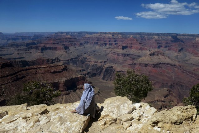 A women sits on the south rim of Grand Canyon National Park in northern Arizona, April 12, 2015. (Photo by Jim Urquhart/Reuters)