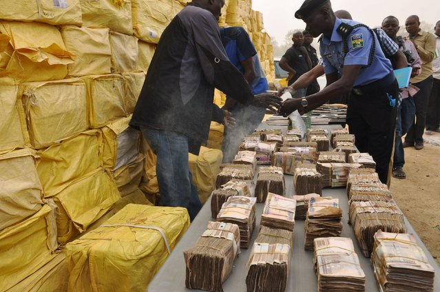 A policeman inspects displayed weapons, money and illegal drugs confiscated earlier by police in Kano, Nigeria February 23, 2016. According to the police commissioner, more than 1,000 parcels of illegal drugs were seized among other confiscated goods. (Photo by Reuters/Stringer)