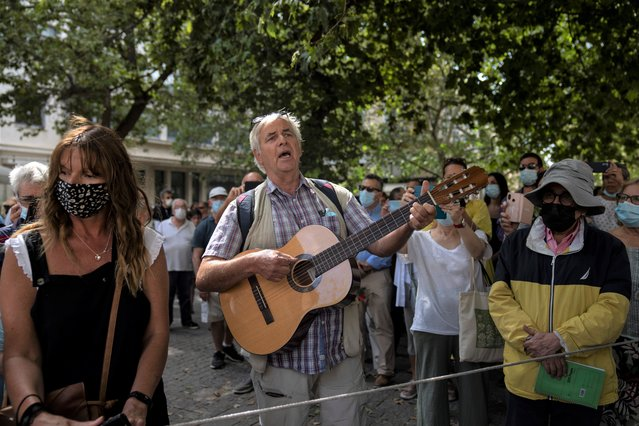 A man plays guitar outside the Athens Cathedral in Athens on Monday September 6, 2021. Hundreds of people have gathered outside Athens Cathedral where Greek composer and politician Mikis Theodorakis is to lie in state in a chapel of the cathedral for three days ahead of his burial on the southern island of Crete. (Photo by Petros Giannakouris/AP Photo)