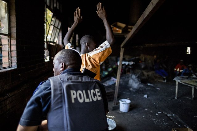 A resident holds up his hands as a South African anti-riot police officer raids the kitchen area of a hostel in Benoni on April 16, 2015 whose local residents are suspected of having protested against foreign-owned shops in the area, pelting with stones the trucks bringing supplies to the shops and forcing them to shut down. (Photo by Marco Longari/AFP Photo)