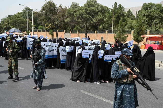 Armed Taliban fighters escort veiled women as they march during a pro-Taliban rally outside Shaheed Rabbani Education University in Kabul on September 11, 2021. (Photo by Aamir Qureshi/AFP Photo)