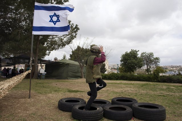 An Israeli boy jumps on car tire during a display of the Israeli Defense Forces (IDF) equipment and abilities at the West Bank settlement of Kiryat Arba April 23, 2015. during celebrations for Israel's Independence Day, marking the 67th anniversary of the creation of the state. (Photo by Ronen Zvulun/Reuters)