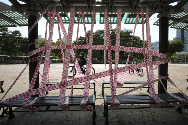 Public benches are taped off according to social distancing rules at a park in Anyang, South Korea, Friday, July 30, 2021. (Photo by Ahn Young-joon/AP Photo)