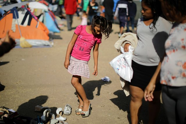 A girl tries on shoes as she waits with members of a caravan from Central America, who are trying to reach the United States, in a temporary shelter in Tijuana, Mexico, November 24, 2018. (Photo by Lucy Nicholson/Reuters)