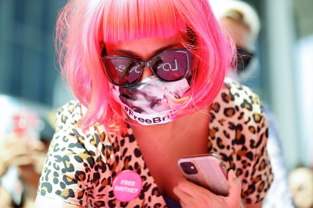A supporter of pop star Britney Spears, wearing a face mask with an image of the singer, writes a message on a sign on the day of a conservatorship case hearing at Stanley Mosk Courthouse in Los Angeles, California, U.S., September 29, 2021. (Photo by Mario Anzuoni/Reuters)