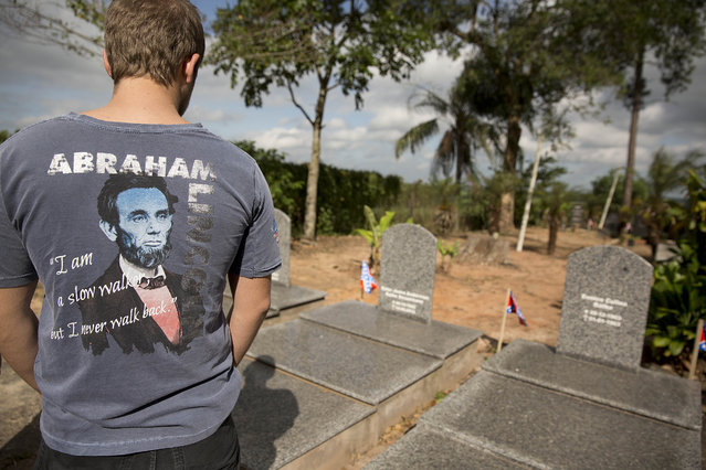 A man wearing a shirt with an image of U.S. President Abraham Lincoln looks at the tombs of his American Southern relatives, during a party to celebrate the 150th anniversary of the end of the American Civil War in Santa Barbara d'Oeste, Brazil, Sunday, April 26, 2015. (Photo by Andre Penner/AP Photo)