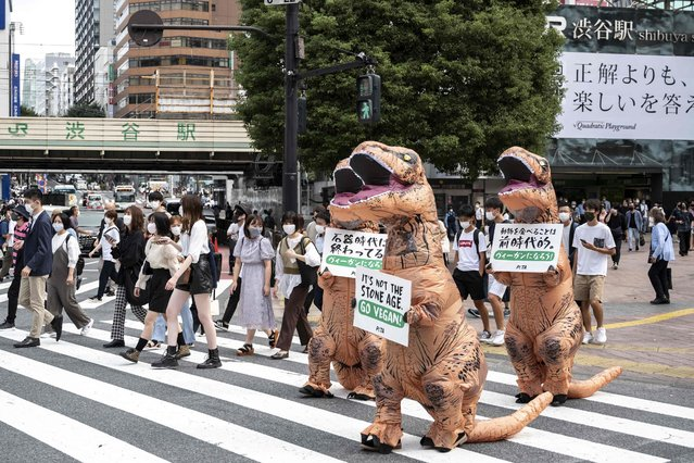Animal rights group PETA activists urge people to become vegan during a protest in Tokyo on October 6, 2021. (Photo by Charly Triballeau/AFP Photo)