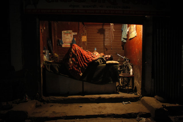 A man sleeps in his store with the shutters open in Kathmandu, Nepal, Tuesday, April 28, 2015. (Photo by Niranjan Shrestha/AP Photo)