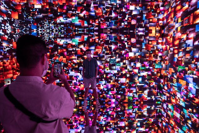 """People visit an art piece by Turkish-American new media digital artist Refik Anadol's entitled """"Machine Hallucination Space: Metaverse Lot 1"""" at the Digital Art Fair Asia in Hong Kong, China, 05 October 2021. The fair features 40 international and local artists showcasing new media art, NFT Crypto Art or non-fungible tokens, a unique and non-interchangeable unit of data stored on a blockchain and immersive art experiences. The fair runs through 17 October 2021. (Photo by Jerome Favre/EPA/EFE)"""