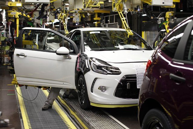 An employee works on the automobile assembly line of a DS 3 car at the PSA Peugeot Citroen plant in Poissy, near Paris, France, April 29, 2015. (Photo by Benoit Tessier/Reuters)