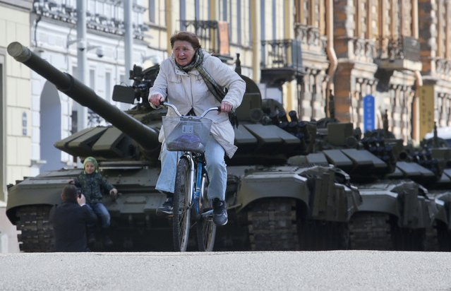 A woman rides a bicycle past Russian T-72 tanks prior to a rehearsal for the Victory Day military parade which will take place at Dvortsovaya (Palace) Square on May 9th to celebrate 70 years after the victory in WWII, in St. Petersburg, Russia, Thursday, April 30, 2015. (Photo by Dmitry Lovetsky/AP Photo)