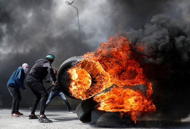 A Palestinian protester moves a burning tire during clashes with Israeli troops near the Jewish settlement of Beit El, in the Israeli-occupied West Bank March 27, 2019. (Photo by Mohamad Torokman/Reuters)