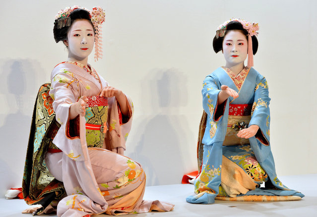 "Apprentice geishas, or ""maiko"", from Japan's ancient capital Kyoto, Mamefuji (L) and Shoko (R) perform a traditional dance at the opening event of the ""Kyo Aruki in Tokyo 2014"", to promote tourism in Kyoto at a shopping mall in Tokyo on February 4, 2014. The event will continue until February 19 as part of a campaign to tempt visitors back to Kyoto. (Photo by Yoshikazu Tsuno/AFP Photo)"