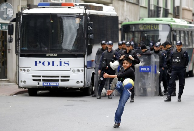 A boy kicks a ball as policemen block streets to prevent people from gathering for May Day demonstrations near Taksim Square in Istanbul, Turkey, May 1, 2015. Istanbul went into a security lockdown on Friday as thousands of Turkish police manned barricades and closed off streets to traffic to stop May Day rallies at the central Taksim Square, a symbolic point for anti-government protests. (Photo by Umit Bektas/Reuters)