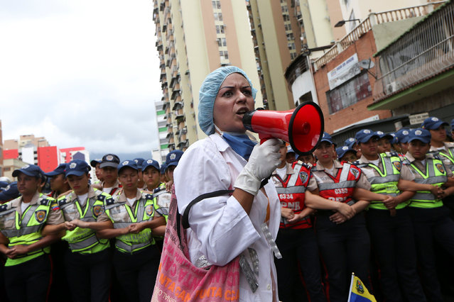 A woman shouts slogans in front of the riot police during a rally of workers of the health sector and opposition supporters, due to the shortages of basic medical supplies and against Venezuelan President Nicolas Maduro's government in Caracas, Venezuela February 7, 2017. (Photo by Carlos Garcia Rawlins/Reuters)