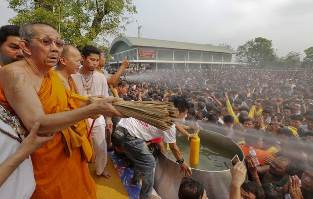 A Buddhist monk sprays devotees with holy water during the annual Magic Tattoo Festival at Wat Bang Phra in Nakhon Pathom province, on the outskirts of Bangkok, Thailand, March 19, 2016. (Photo by Chaiwat Subprasom/Reuters)