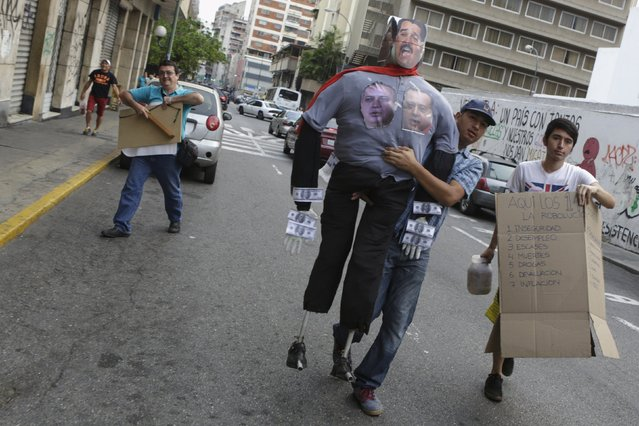 """A man carries an effigy depicting Venezuela's President Nicolas Maduro before being burnt during the traditional """"Burning of the Judas"""" as part of Easter celebrations in Caracas, March 27, 2016. (Photo by Marco Bello/Reuters)"""