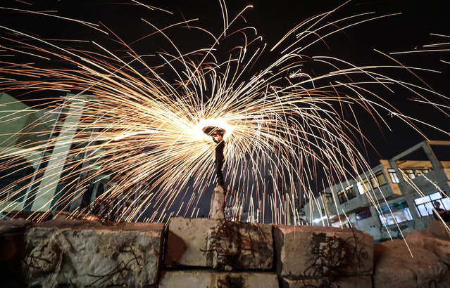 Gazaian youth perform fire spinning during the holy month of Ramadan in Gaza City, Gaza on May 6, 2019. (Photo by Mustafa Hassona/Anadolu Agency/Getty Images)