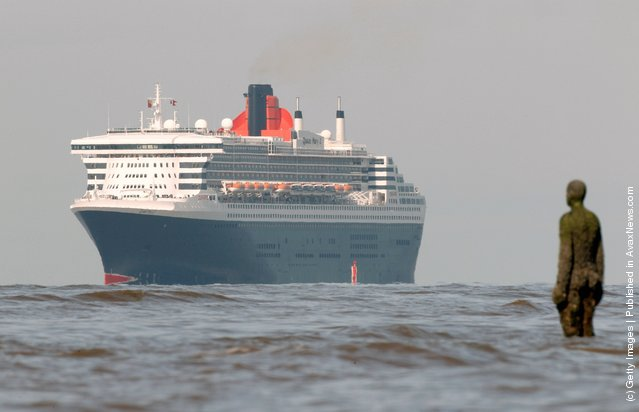 The Queen Mary 2 (QM2) sails past Antony Gormley's 'Another Place' on the approach to the Port of Liverpool
