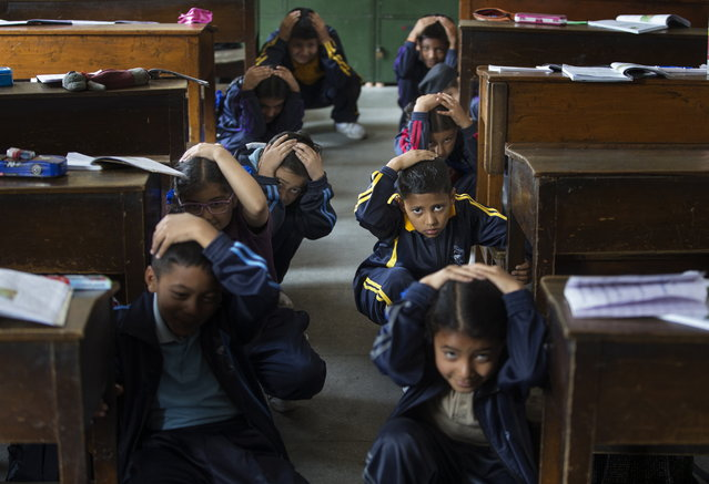 Nepalese school children crouch under their desk during an earthquake drill at St. Xavier's School to mark the 4th anniversary of devastating earthquake that shook Nepal in 2015 in Lalitpur, Nepal 25 April 2019. The School Earthquake Safety Division conducted Duck, Cover and Hold earthquake safety exercise to aware school children to aware of earthquake as Nepal is organizing various memorial service  in remembrance of the victims of the quake that left over 8,000 people dead and more than 21,000 people injured on 25 April 2015. (Photo by Narendra Shrestha/EPA/EFE)