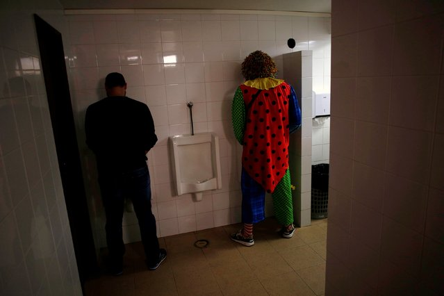 A man dressed as a clown stands in the bathroom during the carnival clowns parade in Sesimbra village, Portugal, February 27, 2017. (Photo by Pedro Nunes/Reuters)