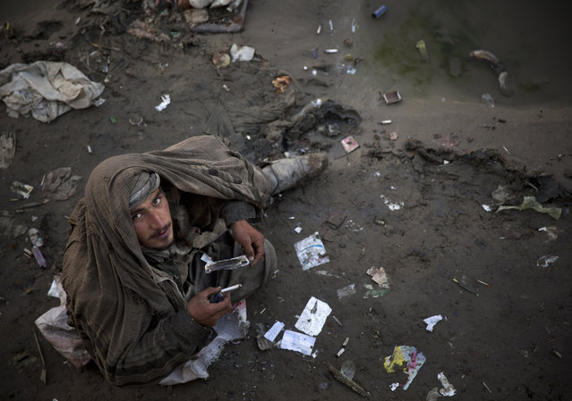 In this Saturday, November 9, 2013 photo, an Afghan drug addict smokes opium in a foul smelling river bed in the center of Kabul. More than 1 million Afghans are addicts, living in squalor in its cities, sleeping on the street, in garbage-filled dried river beds reeking of human waste. (Photo by Anja Niedringhaus/AP Photo)