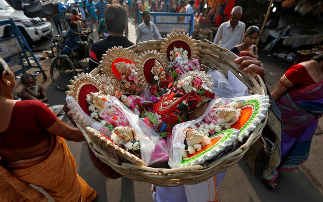 A Hindu priest carries figures of various Hindu deities in a basket after worshipping on the first day of the Bengali calendar in Kolkata, India, April 14, 2016. (Photo by Rupak De Chowdhuri/Reuters)