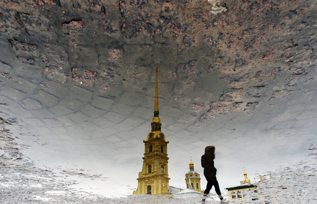 The silhouette of a woman is reflected in a puddle as she crosses a square in front of the Peter and Paul Cathedral in Saint Petersburg on March, 17, 2019. (Photo by Olga Maltseva/AFP Photo)