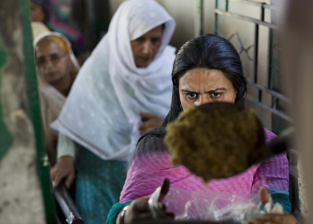 A Pakistani woman receives food distributed at the Barri Imam shrine in Islamabad, Pakistan, Thursday, April 23, 2015. People who visit shrines and pray that their wishes are fulfilled usually offer food to be distributed to the poor. Hundreds of poor families receive free food daily at the shrine. (Photo by B. K. Bangash/AP Photo)