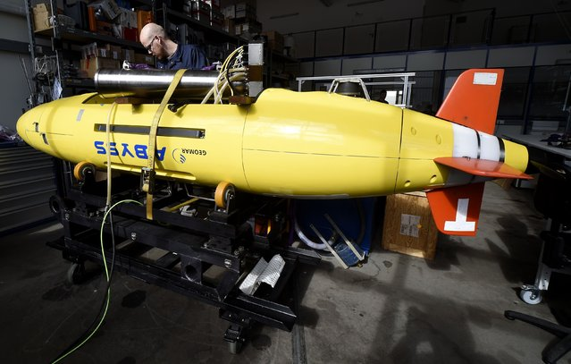 """Electrical engineer Lars Triebe inspects the Autonomous Underwater Vehicle (AUV) """"Abyss"""" in preparation for operational service, at the Helmholtz Centre for Ocean Research Kiel (GEOMAR) in Kiel March 24, 2014. The """"Abyss"""", one of only three worldwide unmanned deep sea search submarines, may join the hunt for the missing Malaysia Airlines flight MH370. The submarine is designed to perform hydrographic reconnaissance in all parts of the ocean in depths up to 6000 meters and can stay submerged for up to 22 hours. (Photo by Fabian Bimmer/Reuters)"""