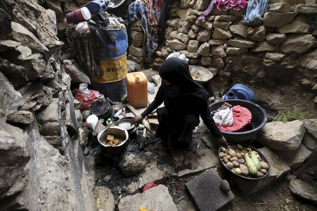 An internally displaced woman washes dishes as she sits in a cave in the district of Khamir of Yemen's northwestern province of Amran May 9, 2015. (Photo by Mohamed al-Sayaghi/Reuters)
