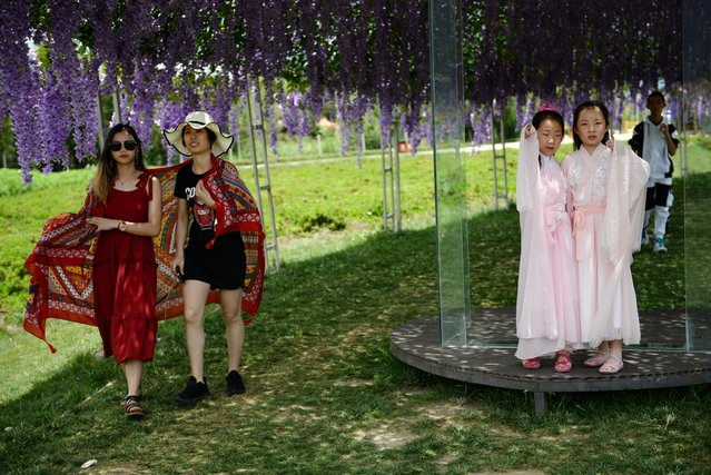Tourists walk under a flower-covered walkway which serves as a prop for photoshoots near Erhai Lake in Dali Bai Autonomous Prefecture, Yunnan province, China on June 15, 2019. (Photo by Tingshu Wang/Reuters)