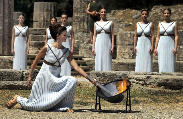 Greek actress Katerina Lehou , playing the role of High Priestess, lights a torch during the dress rehearsal for the Olympic flame lighting ceremony for the Rio 2016  Olympic Games at the site of ancient Olympia in Greece, April 20, 2016. Fire spurted from the concave mirror as a priestess, kneeling in her long, pleated dress before a ruined Greek temple, focused the blazing sun's rays on her metal torch. Come rain or shine on Thursday's official lighting ceremony, Rio de Janeiro has now secured its Olympic flame, which will burn in the main Olympic stadium throughout the Aug. 5-21 games. (Photo by Yannis Behrakis/Reuters)