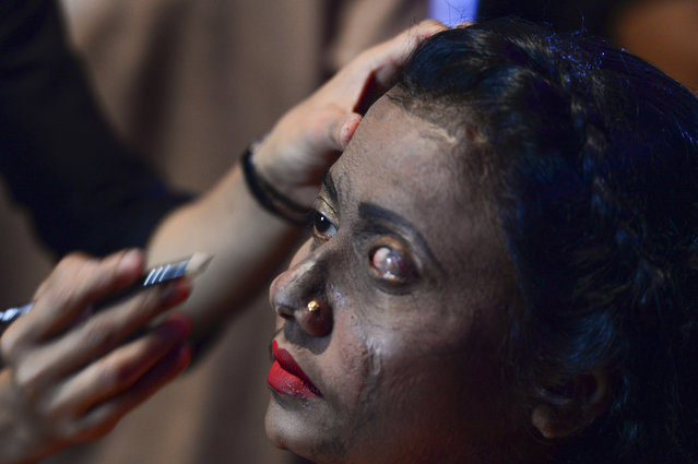 "A Bangladeshi acid attack survivor has her makeup done backstage prior to the fashion show ""Beauty Redefined"" by designer Bibi Russell, featuring acid attack survivors in Dhaka on March 7, 2017. (Photo by AFP Photo/Stringer)"