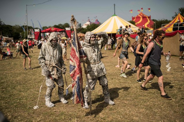 Festival-goers in fancy dress enjoy the fine weather on the third day of the Glastonbury Festival of Music and Performing Arts on Worthy Farm near the village of Pilton in Somerset, South West England, on June 28, 2019. (Photo by Oli Scarff/AFP Photo)