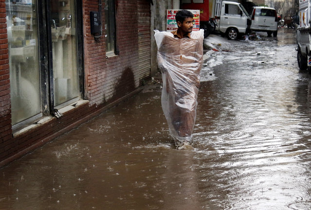 A man wades through a flooded street after heavy rain in Islamabad, Pakistan, 17 April 2019. At least 49 people have been killed as torrential rains wreaked havoc, damaging more than 100 houses, since the beginning of April in parts of Pakistan. The rains and hailstorms, unusual for this time of the year, have destroyed wheat crops in southern areas of Punjab. The province is the most populous in Pakistan and is home to more than half of the country's total 207-million population. (Photo by Sohail Shahzad/EPA/EFE)