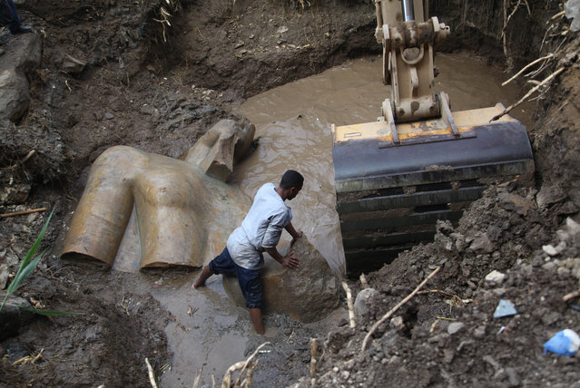 An Egyptian worker prepares to lift parts of a statue at the site of a new archeological discovery at Souq Al-Khamis district in Al-Matareya area, Cairo, Egypt on March 9 2017. According to the Ministry of Antiquities, two 19th dynasty royal statues were found in parts in the vicinity of King Ramses II temple in ancient Heliopolis (Oun) Sun Temples by a German-Egyptian archeological mission. (Photo by Xinhua News Agency/Rex Features/Shutterstock)