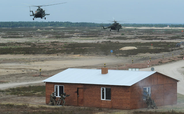 Helicopters fly over soldiers who attack a building during the NATO Noble Jump exercise on a training range near Swietoszow Zagan, Poland, Thursday, June 18, 2015. (AP Photo/Alik Keplicz)