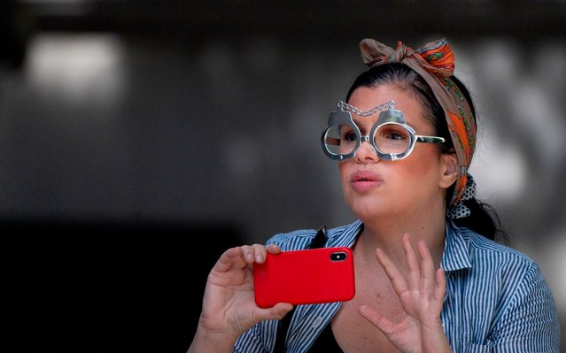A woman wears a glasses in the shape of handcuffs at the courthouse ahead of a bail hearing in US financier Jeffrey Epstein's s*x trafficking case on July 15, 2019 in New York City. Epstein, 66, was charged July 8, 2019 in New York with one count of s*x trafficking of minors and one count of conspiracy to commit s*x trafficking of minors. He faces up to 45 years in prison if convicted. (Photo by Johannes Eisele/AFP Photo)