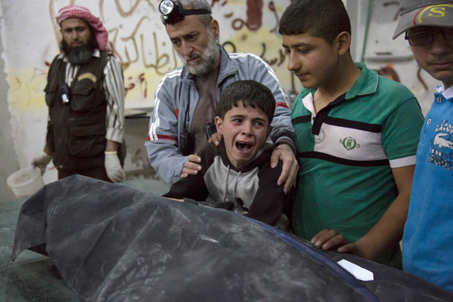 A Syrian boy is comforted as he cries next to the body of a relative who died in a reported airstrike on April 27, 2016 in the rebel-held neighbourhood of al-Soukour in the northern city of Aleppo. (Photo by Karam Al-Masri/AFP Photo)