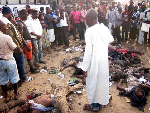 Bystanders look at dead bodies, victims of an attack, in Abuja on April 14, 2014. (Photo by AFP Photo/STR)
