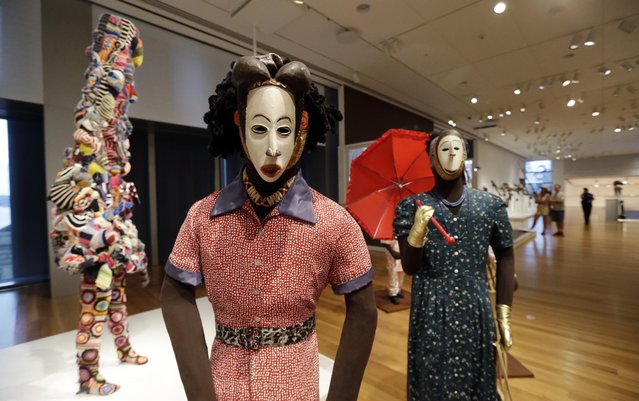 "Nigerian masks from the 1950's are displayed with costumes to create a ""masquerade parade"" as part of the the show ""Disguise: Masks & Global African Art"" at the Seattle Art Museum on Sunday, June 28, 2015. (Photo by Elaine Thompson/AP Photo)"