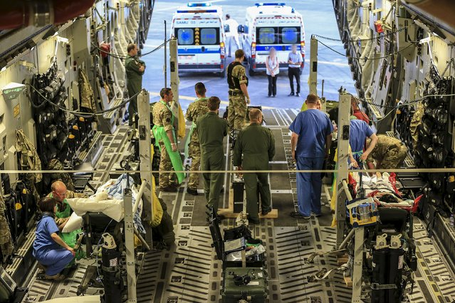 Military personnel attend to seriously injured British nationals on board a Royal Air Force C17 aircraft at Monastir airport in Tunisia, in this June 29, 2015 handout photograph released by Britain's Ministry of Defence in London on June 30, 2015. (Photo by Neil Bryden/Reuters/MoD Crown Copyright)