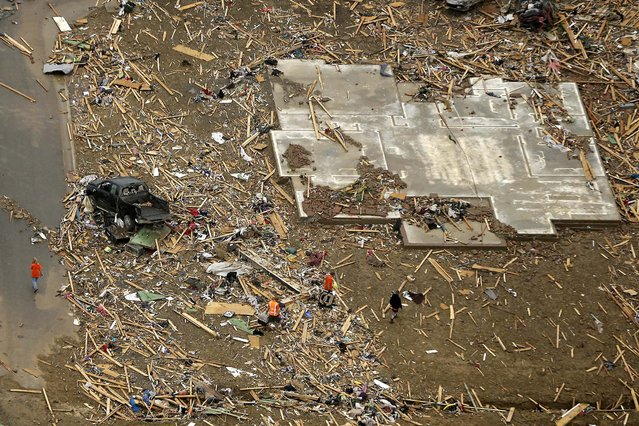 A concrete slab and rubble are all that is left of a home in a Vilonia, Arkansas neighborhood. (Photo by Danny Johnston/Associated Press)