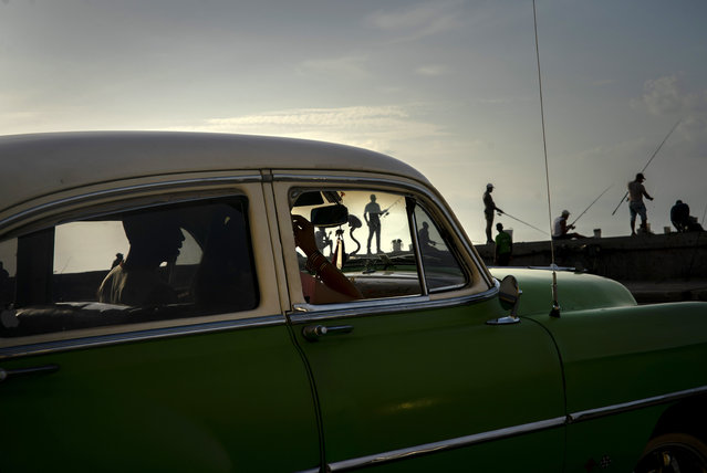 A couple in a classic, American car drive along the Malecon seawall where fishermen work at sunset in Havana, Cuba, Wednesday, June 19, 2019. (Photo by Ramon Espinosa/AP Photo)